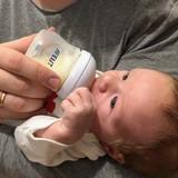 Tētis baro mazuli ar Philips Avent piena pumpi atslauktu mātes pienu.