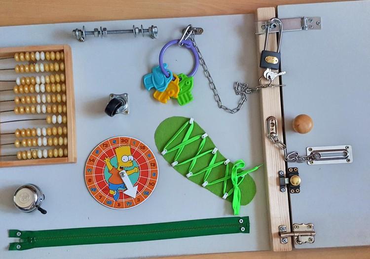 Aktivitātes dēlis un citas rotaļlietas mazo pirkstiņu vingrināšanai